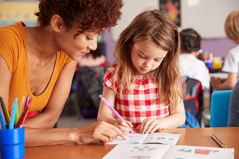 06 elementary school teacher giving female pupil one XQFZHTV - The K Calendar